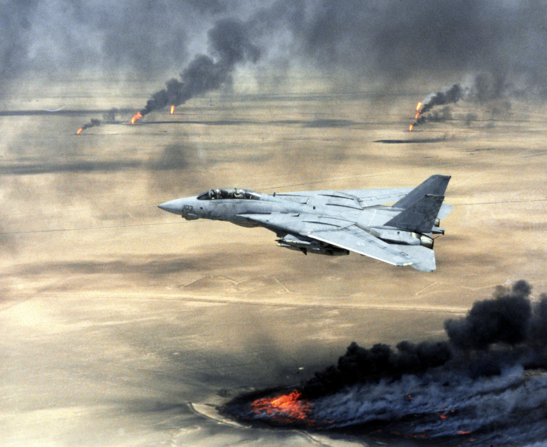 Copy negative of a US Navy (USN) F-14A Tomcat, Fighter Squadron 211 (VF-211), Naval Air Station (NAS) Oceana, Virginia Beach, Virginia (VA), in flight over burning Kuwaiti oil wells during Operation DESERT STORM.