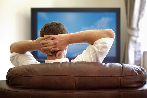Man siting uncomfortable watching cricket with his girlfriend